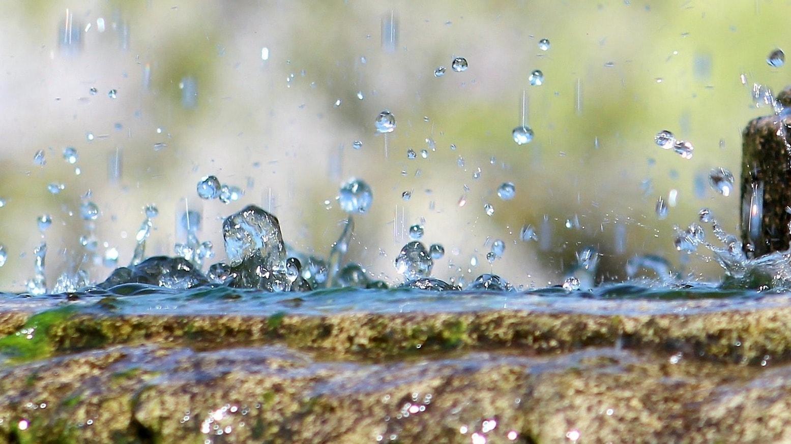Wassertropfen spritzen auf einem Brunnen