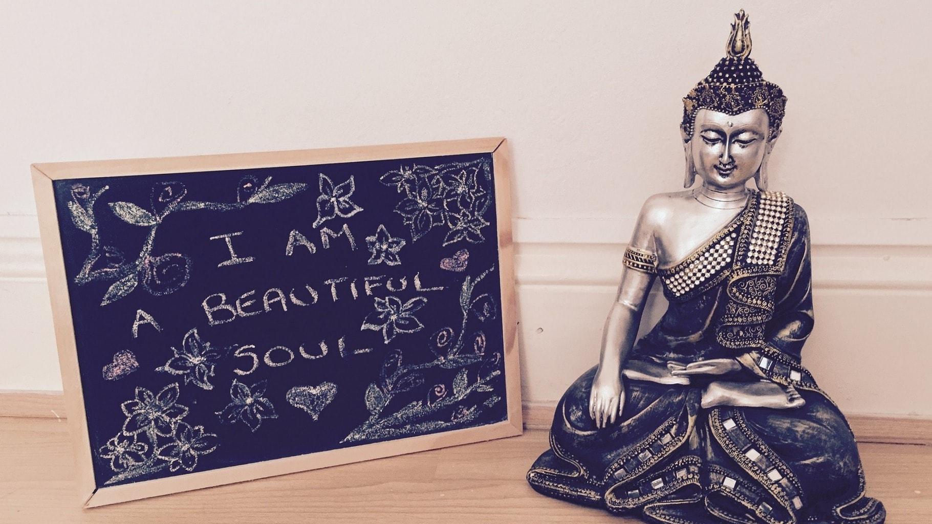 """Buddha-Statue vor einer Wand; daneben eine Tafel mit der Aufschrift """"I am a beautiful soul"""""""