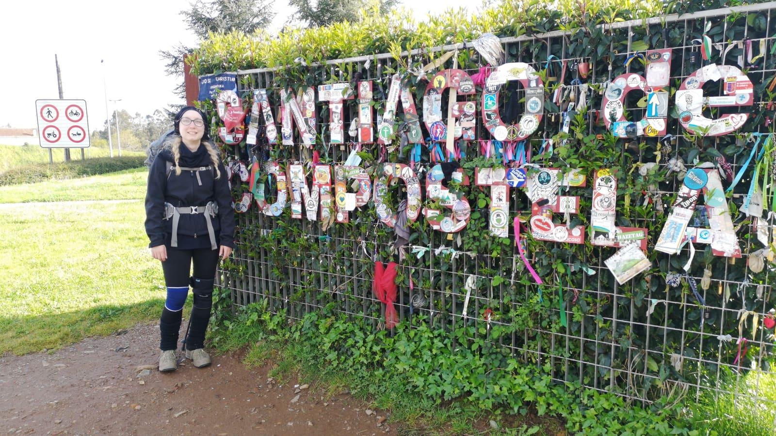 """Wir laufen in einem Bogen um die Stadt herum und hinab an die Straße, kommen schließlich an dassymbolische """"Santiago de Camino""""-Schild und hinterlassen einen symbolischen Sticker."""