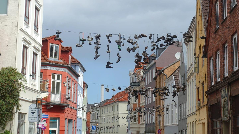 Schuhe baumeln über einer Leine in der Norderstraße in Flensburg. Warum sie das tun? Weiß niemand so genau. Aber es gibt viele Ideen.