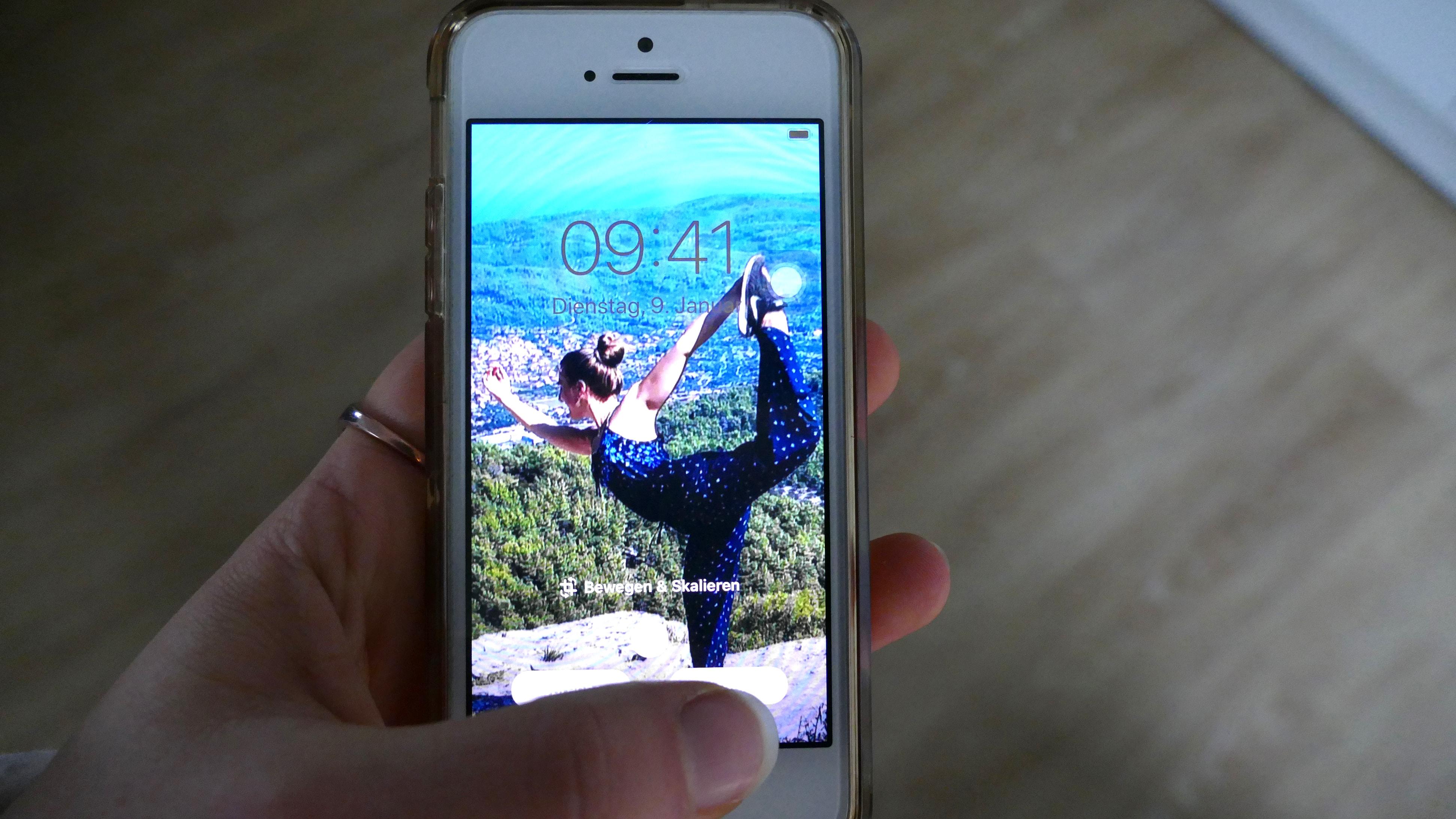 Julia richtet ein Reisefoto auf ihrem Handy als Hintergrund ein