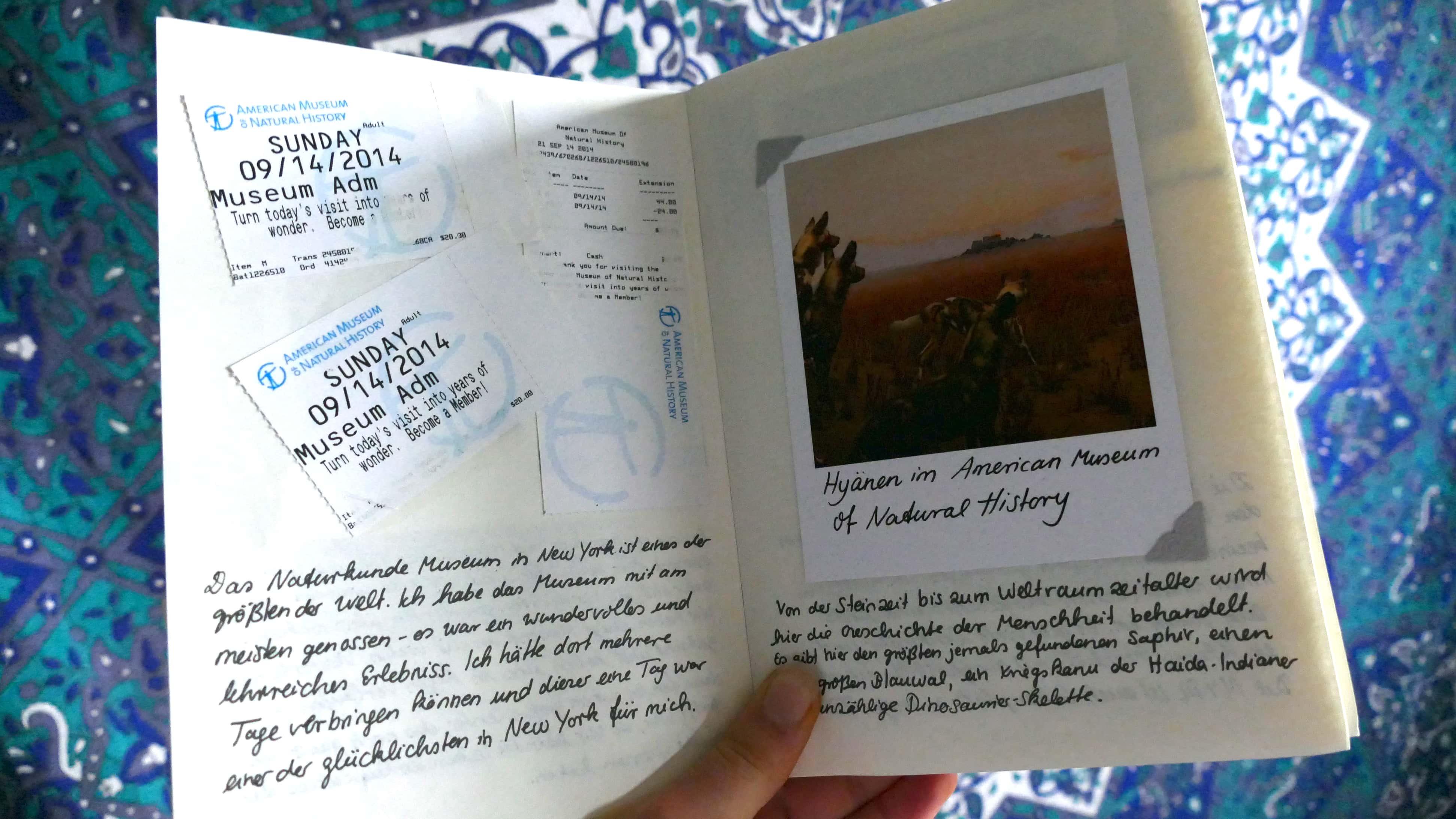 Julia zeigt ein Polaroid, das sie in einem Album eingeklebt hat, daneben Tickets eines Museums in New York