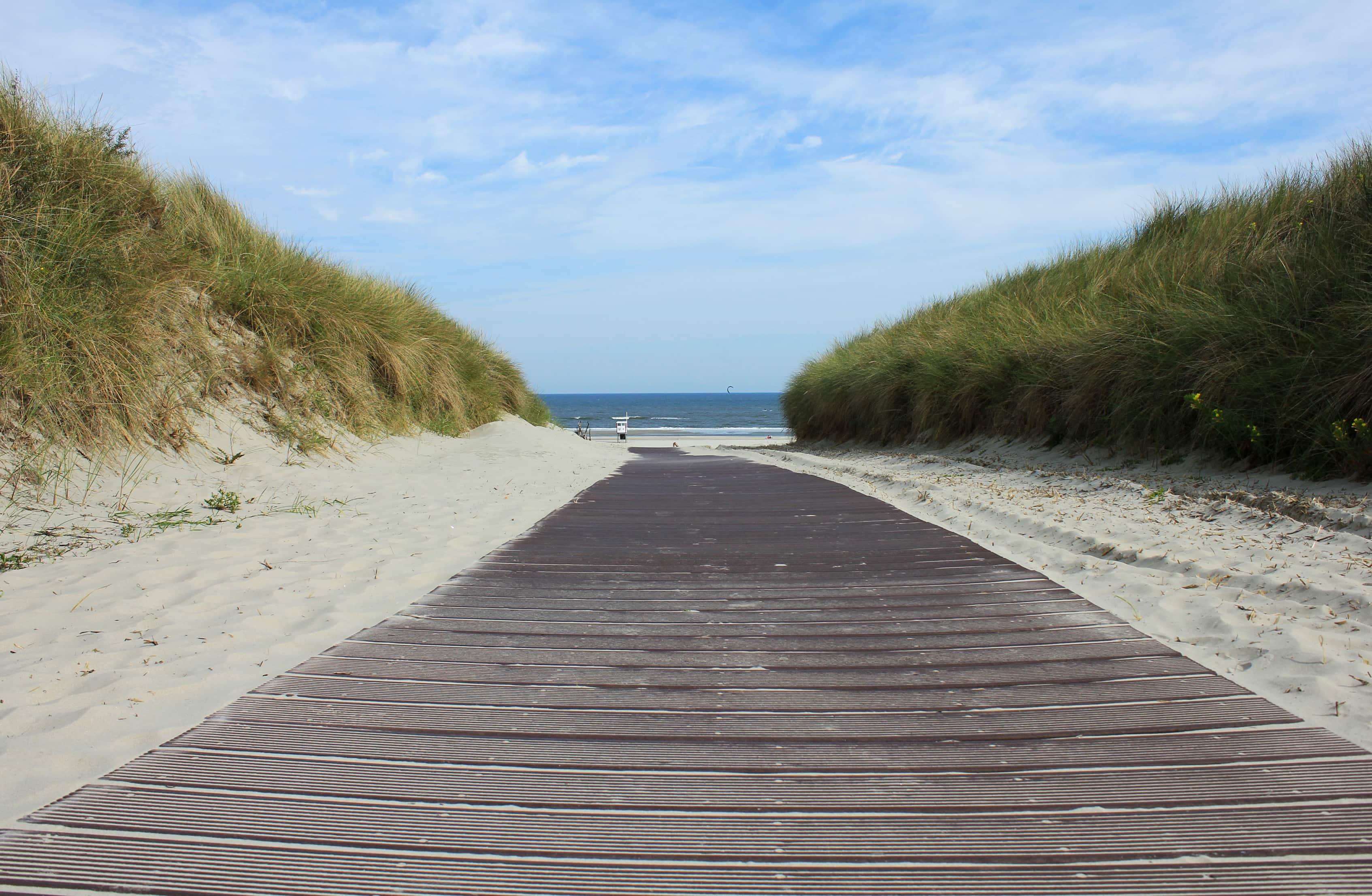 Ein Holzsteg führt durch die Dünen zum kilometerlangen Strand von Juist.