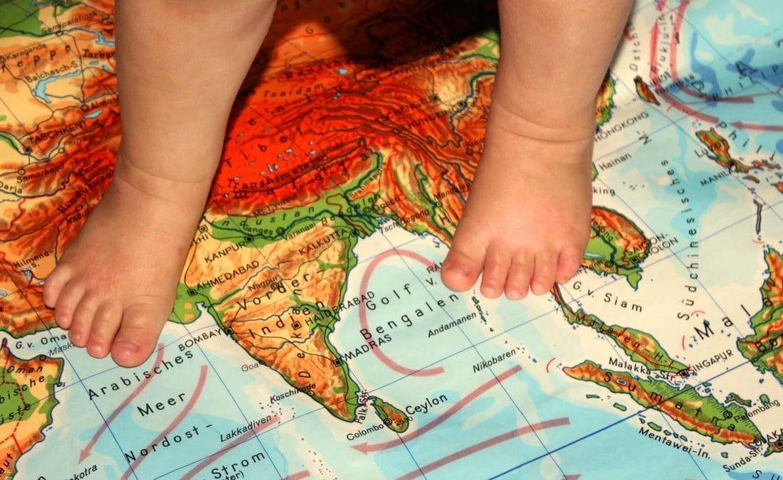 Rubbelbatz, der kleine Sohn von Johanna Bose, mit seinen Füßen auf einer Landkarte
