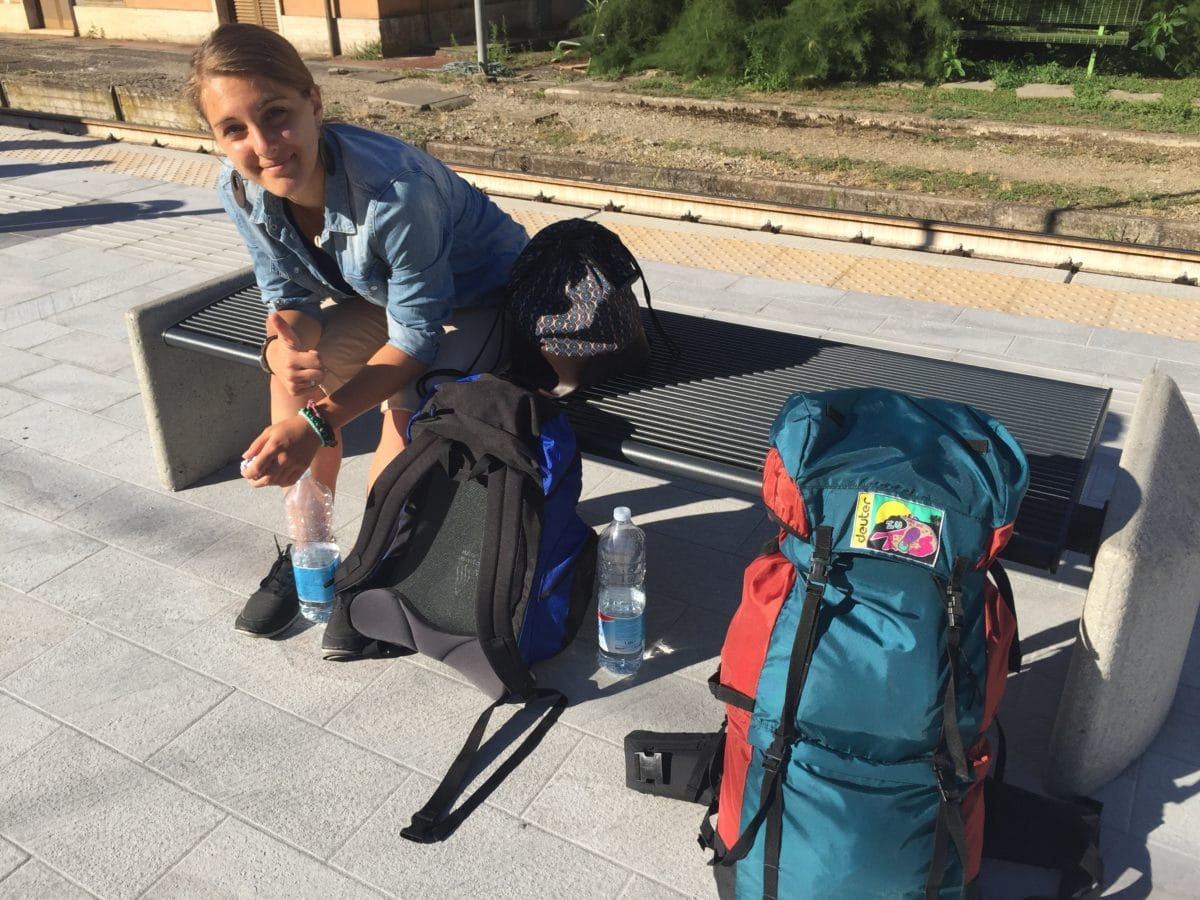 Julia mit Gepäck am Bahnhof