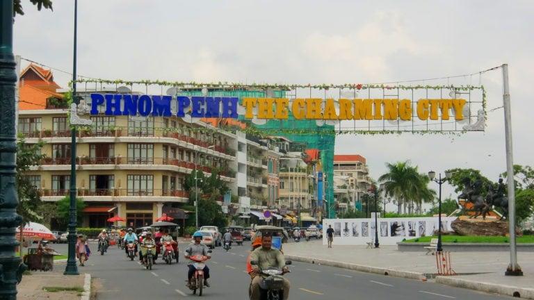 Charmin City steht über der Straße von Phnom Penh, darunter Rollerfahrer.