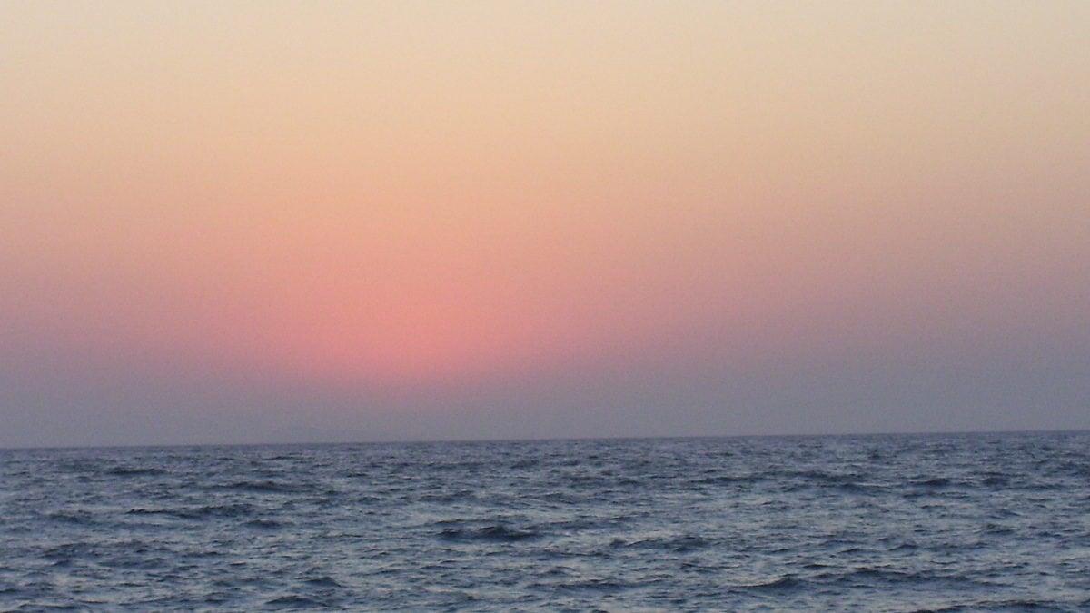 Ein rötlicher Sonnenaufgang über dem Meer