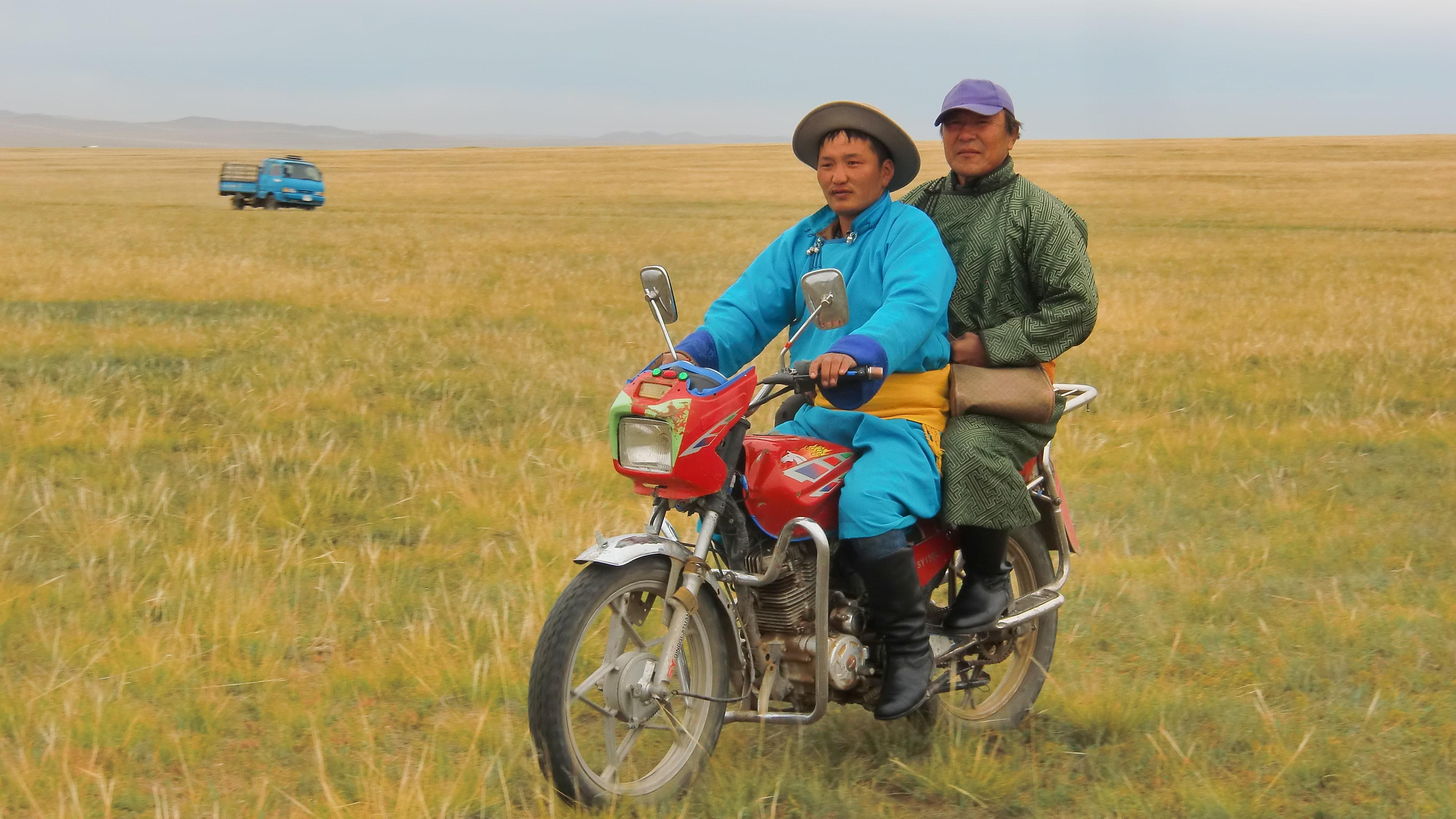 Männer auf einem Motorrad in der Mongolei