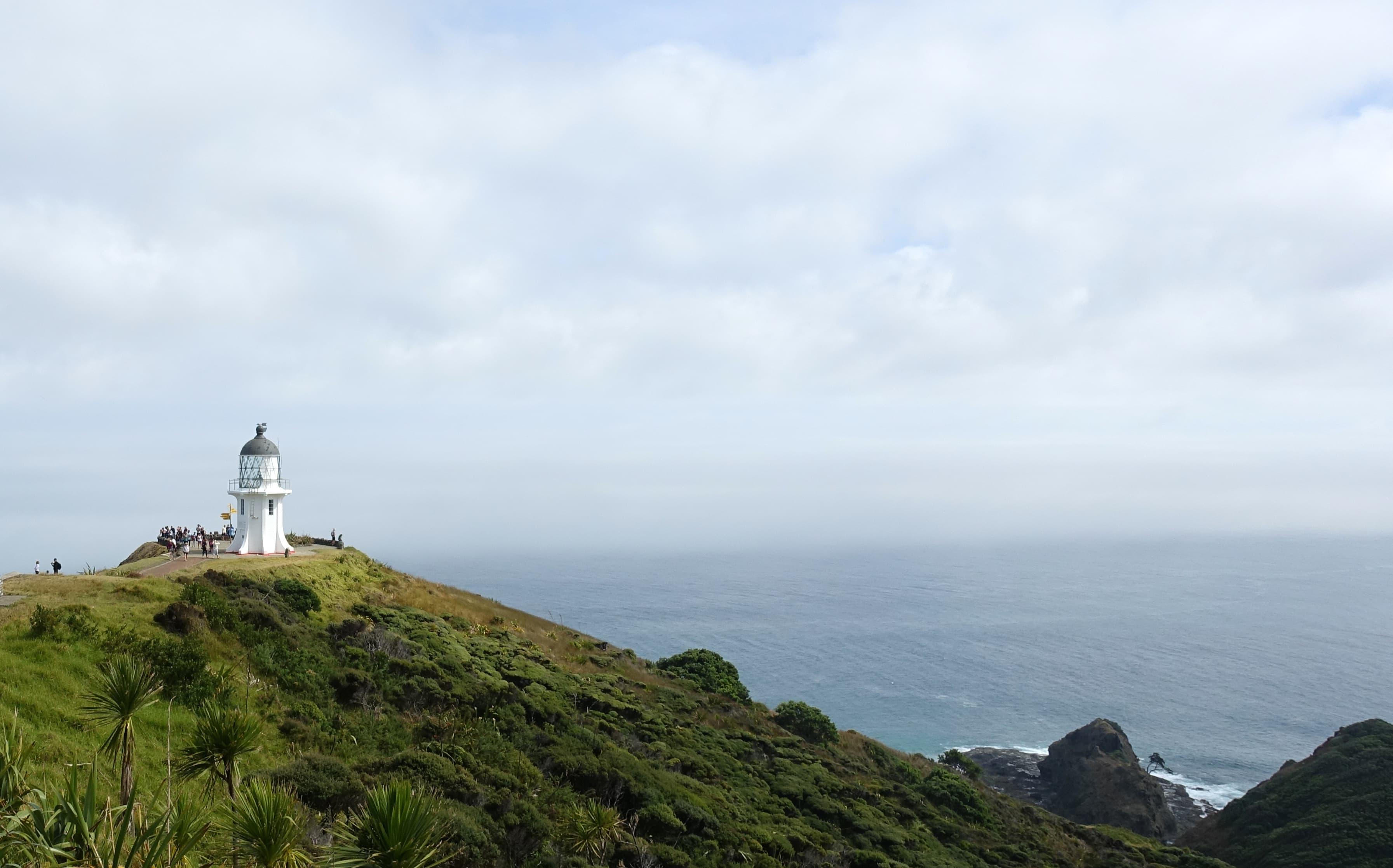 Touristen tummeln sich am Cape Reinga in Neuseeland