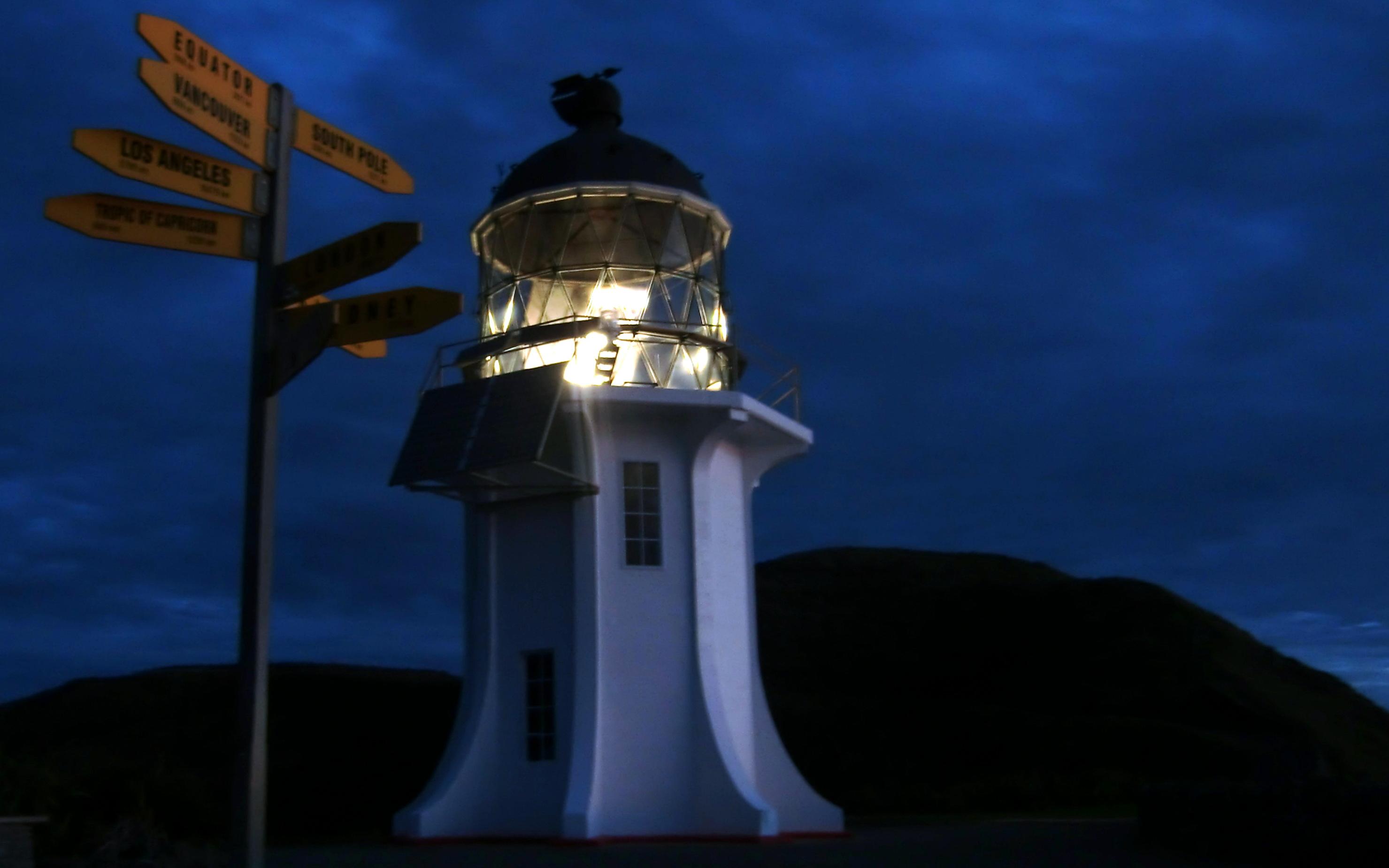 Der weiße Leuchtturm von Cape Reinga in Neuseeland strahlt bei Nacht.