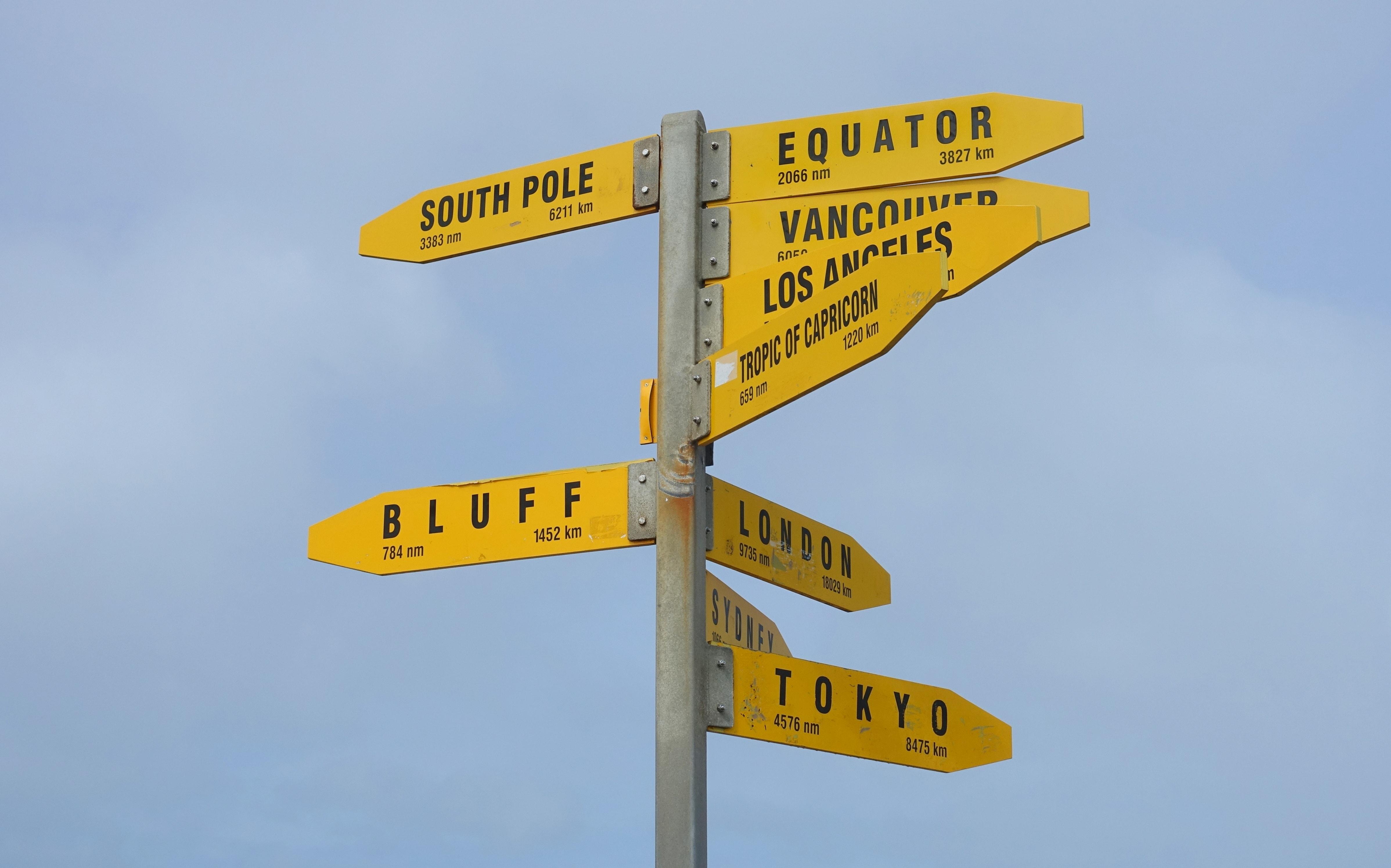 Ein Wegweiser am Cape Reinga in Neuseeland zeigt die Entfernung zu verschiedenen Orten in der Welt an.