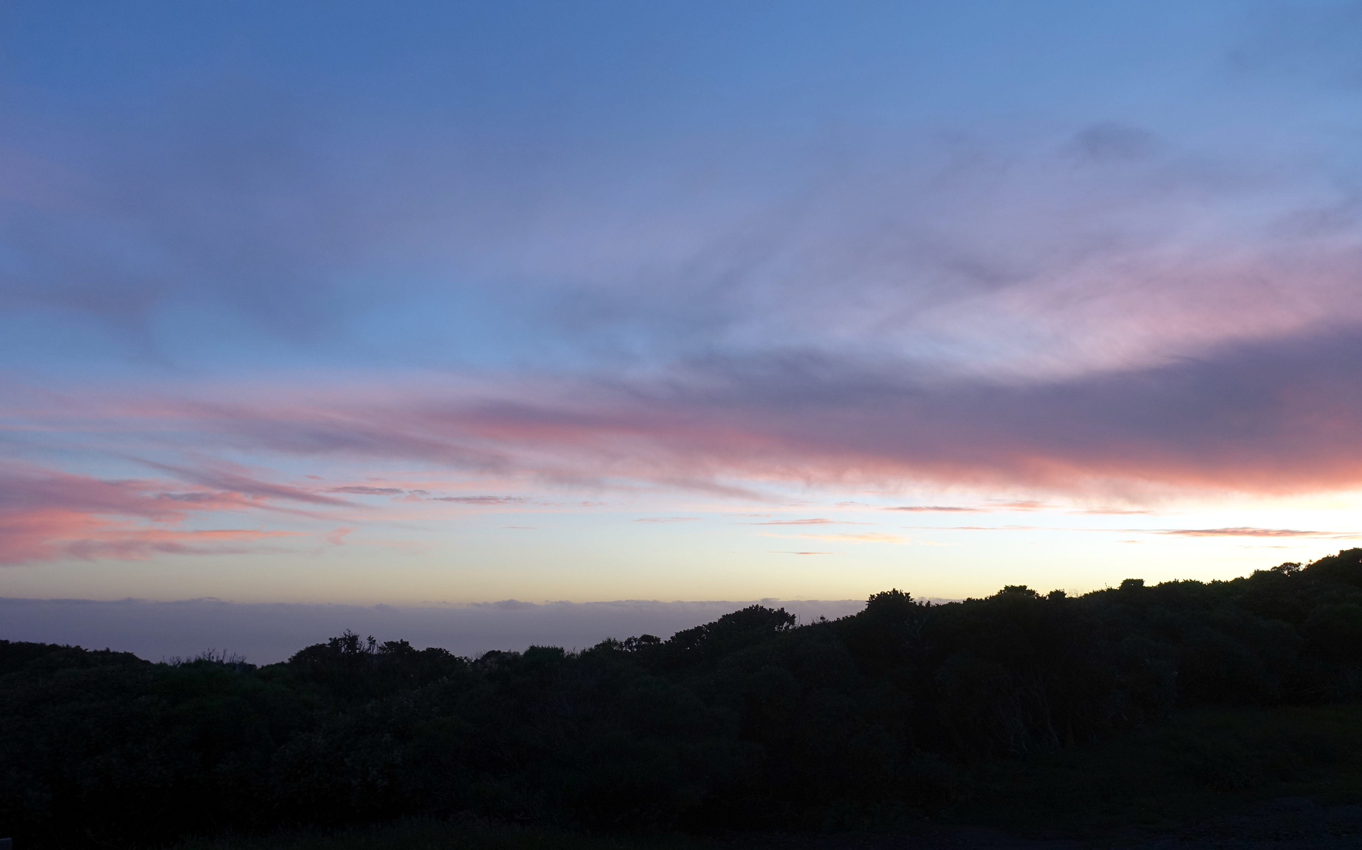 Kurz vorm Sonnenuntergang färbt sich der Himmel in Neuseeland lila. Nur ein schmaler goldener Strich ist am Horizont zu erkennen.