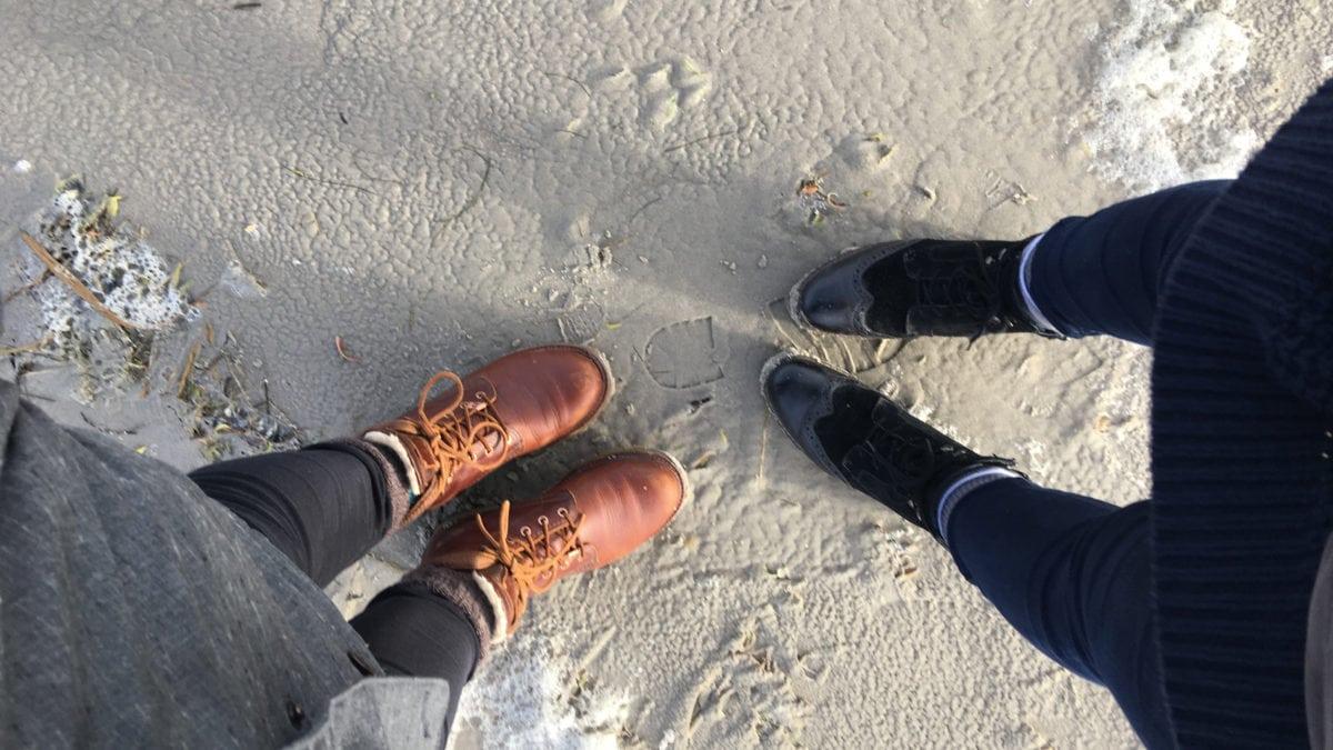 Zwei paar Stiefel stehen sich am Strand von Sankt Peter Ording gegenüber