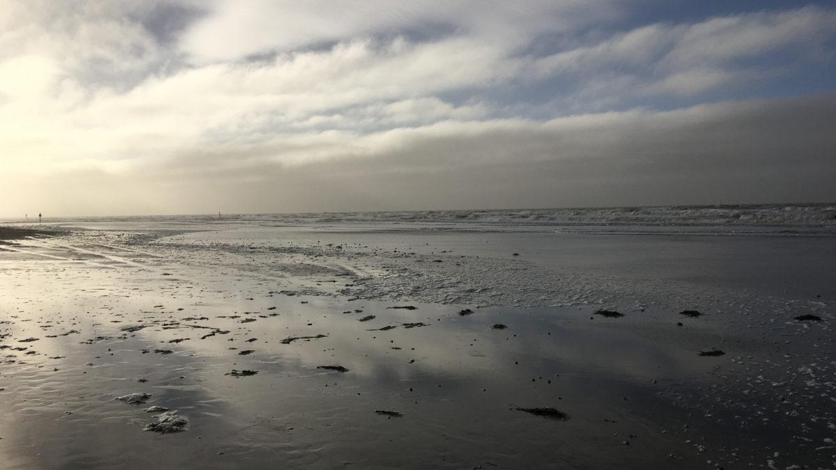 Ein sonnenbeschienener Wolkenhimmel über dem Strand von Sankt Peter Ording in Nordfriesland