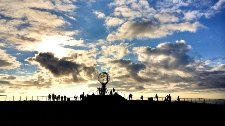 Am Nordkap geht die Sonne im Sommer niemals unter. Während die am blauen Himmel hell scheint sind die Menschen auf dem Bild ganz dunkel.