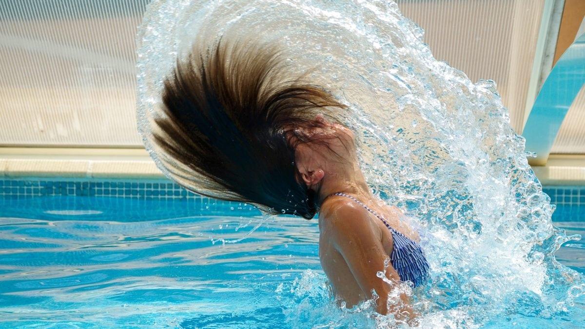 Mädchen im Schimmbad taucht aus dem Pool auf und schwingt Haare über den Kopf