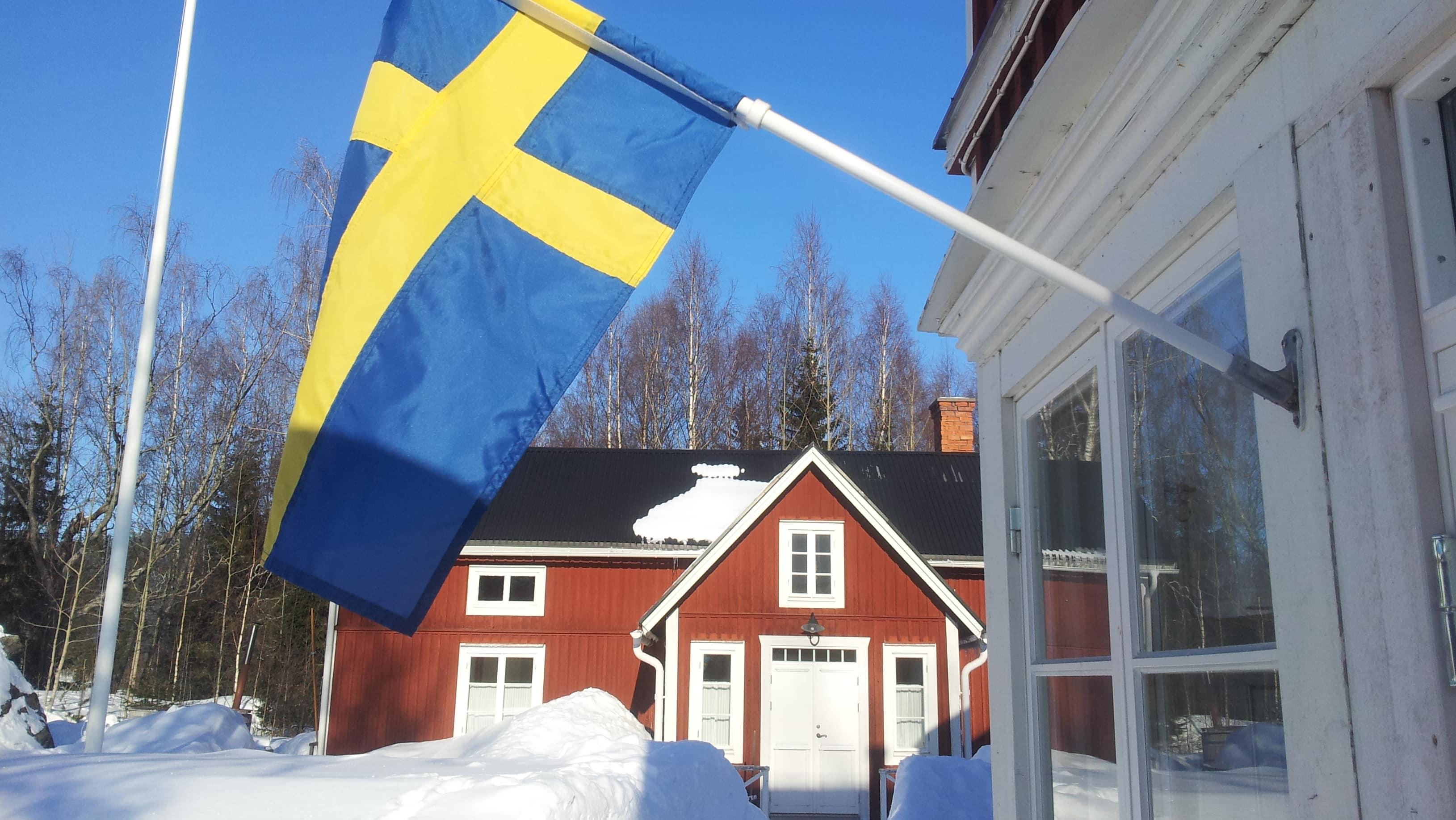 Rotes Haus hinter schwedischer Flagge