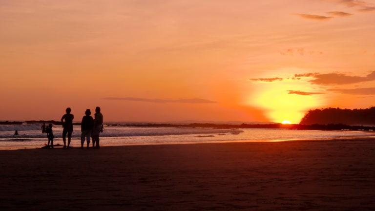 Während die Sonne blutrot hinter dem Meer untergeht steht eine Gruppe Surfer am Wasser