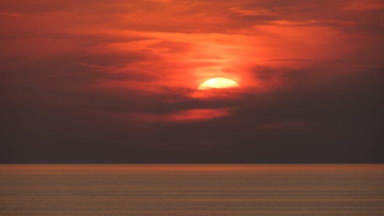 Die Sonne verschwindet über dem Meer rötlich hinter Wolken in der Nacht