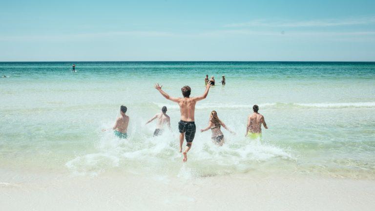 Junge Leute rennen ins Meer an einem Strand