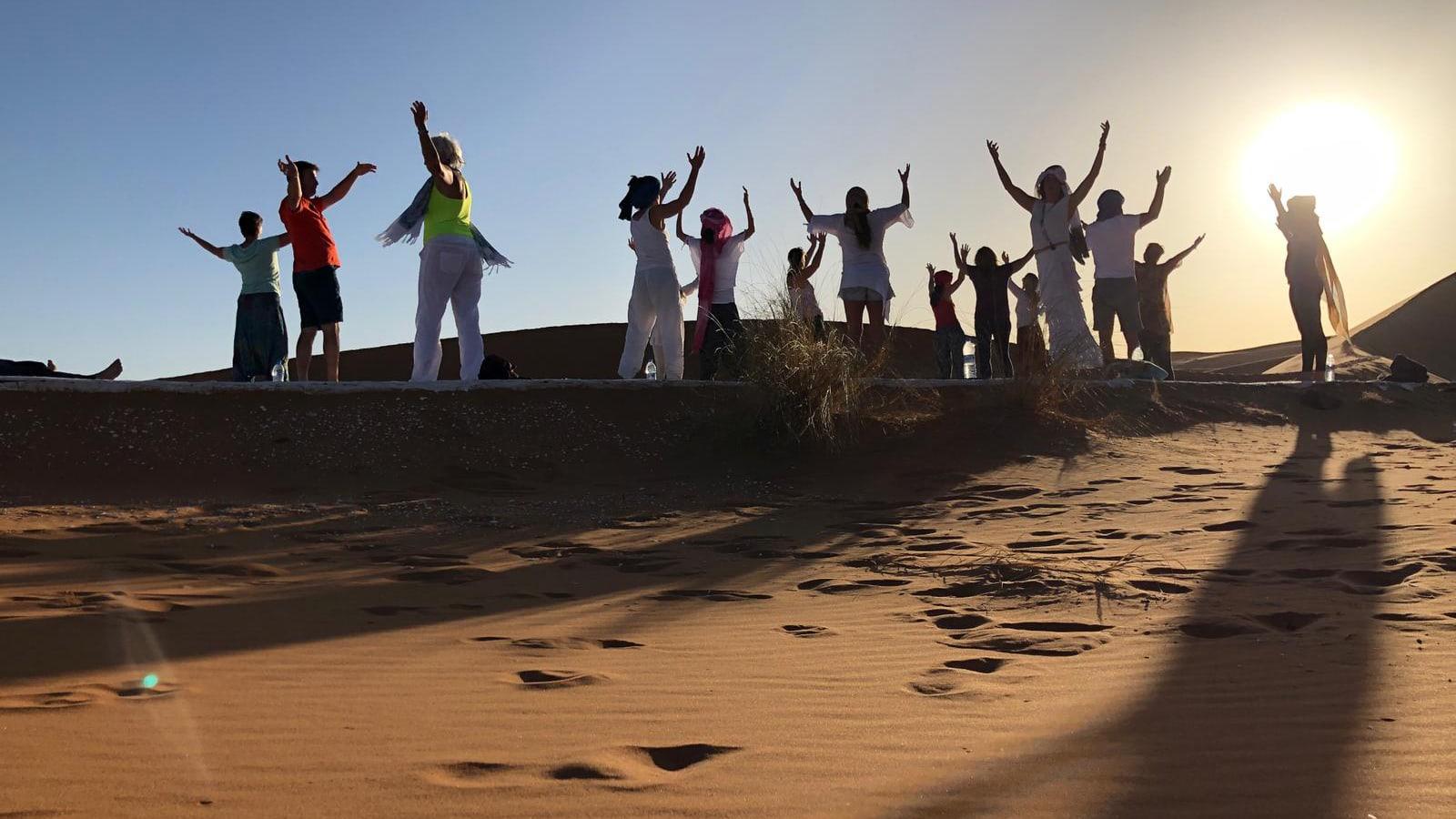 Eine Gruppe tanzt und macht Yoga in der Sahara