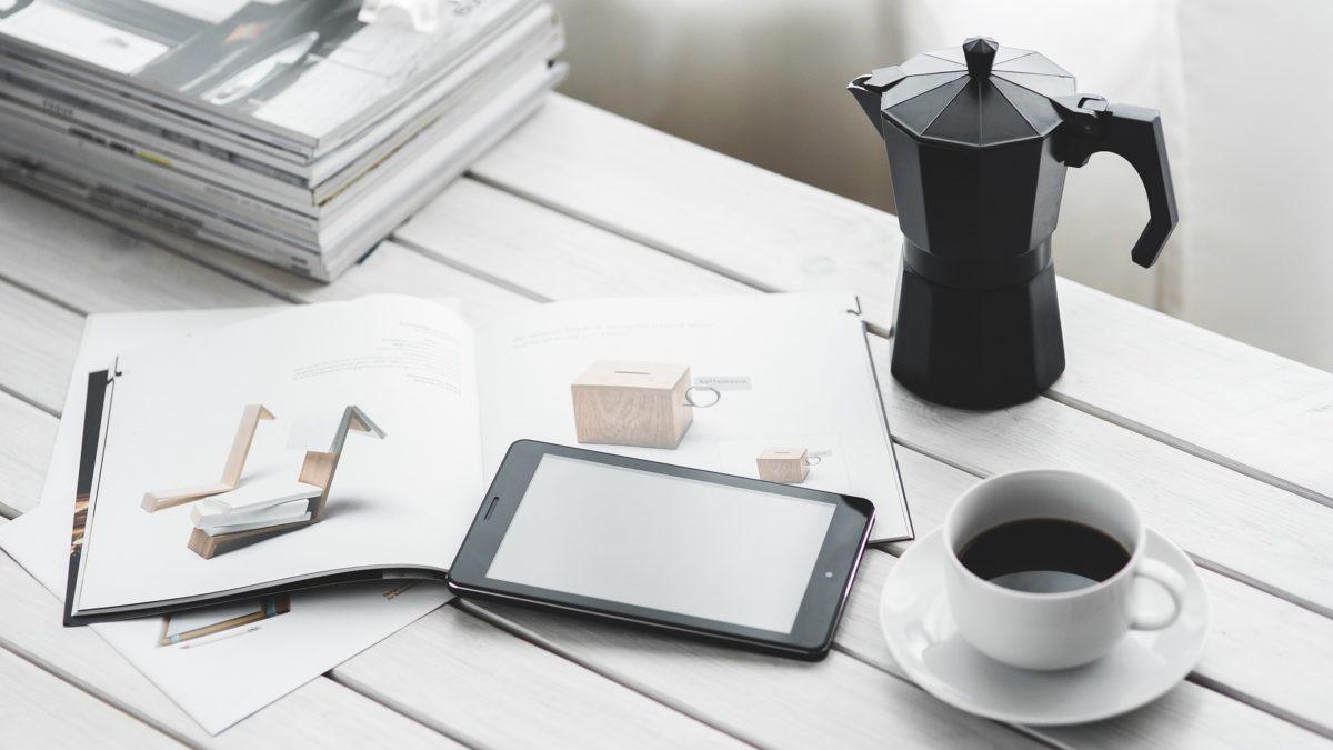 Arbeitsmaterialien liegen neben einer vollen Kaffeetasse und einer Kanne auf einem Schreibtisch, ein normaler Tag im Büro