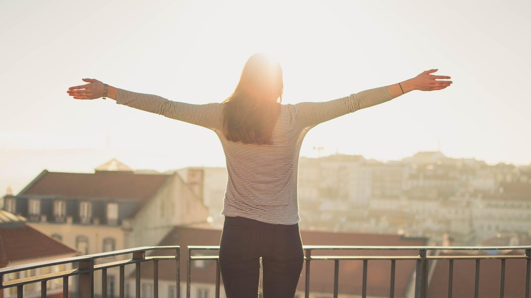 Eine Frau steht auf einem Balkon über den Dächern und streckt die Arme aus
