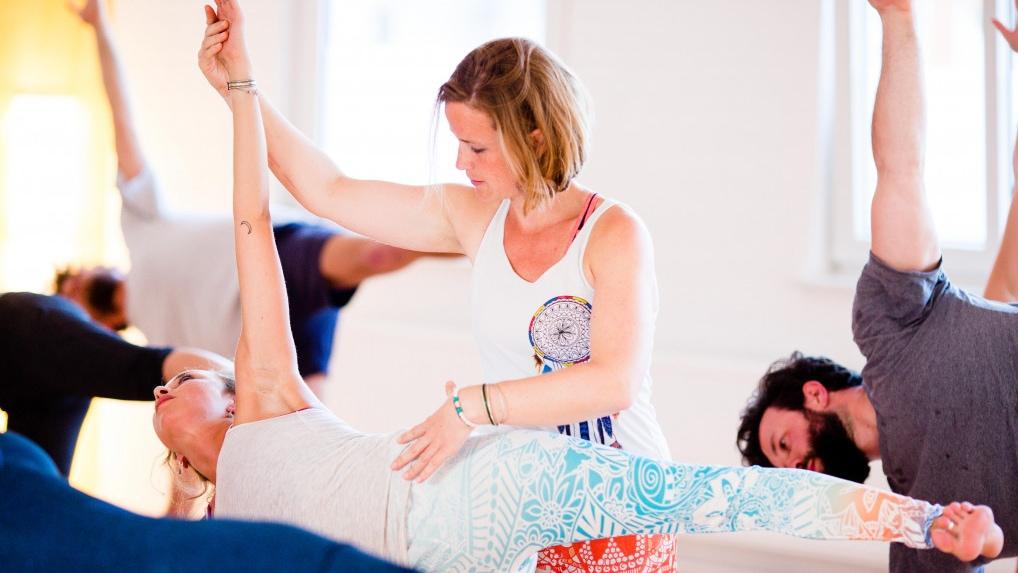 Gesa adjustet eine Teilnehmerin in einer Yogastunde in der Asana Halbmond.