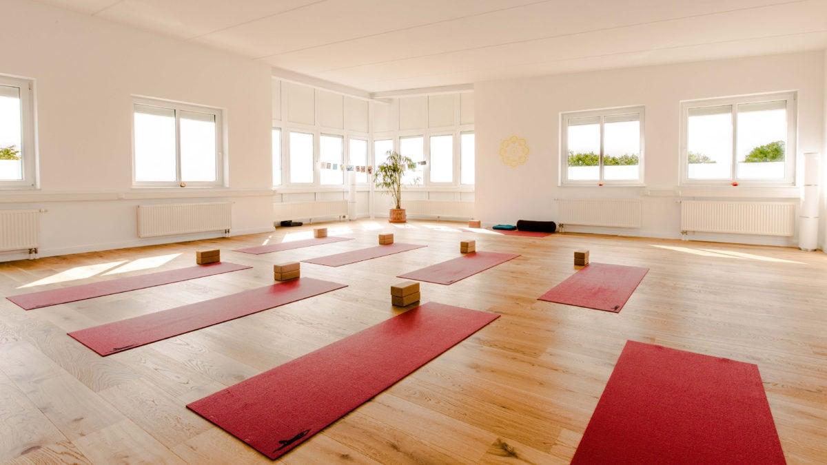 Im Studio von Yoga-Moment sind die roten Yogamatten und Korkblöcke präsent.